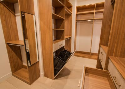 High-end closets, drawers, and a hamper complete this luxury walk-in closet