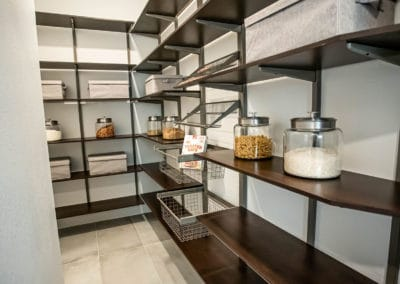 An open concept pantry in Sandalwood that shows dark shelving to create luxury while still giving an open and airy feel.