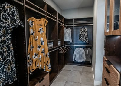 A view of the 'her' side of a two-toned, lighted custom his and hers closet in Sandalwood Community, Summerlin.
