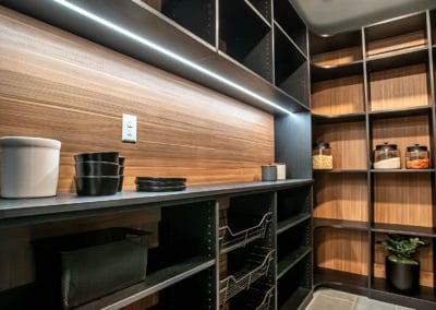 A spin on a modern black pantry with an open concept and two-toned backing.