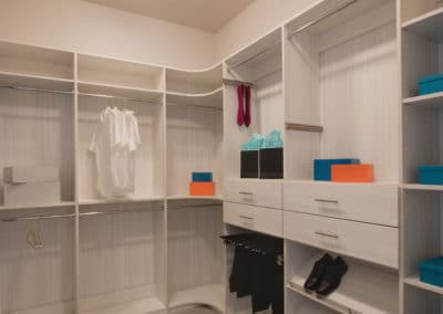 Modern men's closet with a clean look and a pants rack that pulls out for easy access to hanging pants.