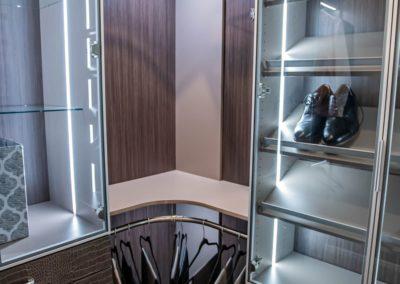 Sophisticated aluminum-framed glass doors lighted shoe rack and custom drawers for closet
