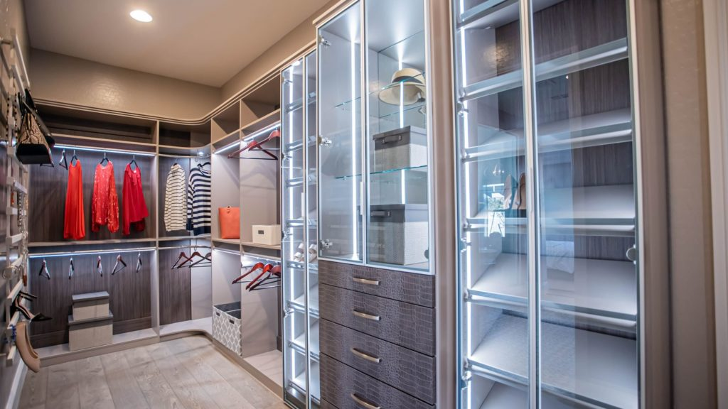 Elegant looking for her closet with crocodile pattern drawer fronts and lighted display cabinets