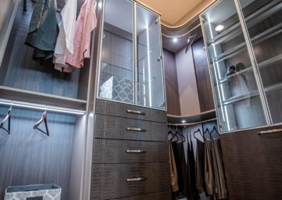 custom drawers for closet and aluminum framed shelf glass doors in an expensive walk in closet