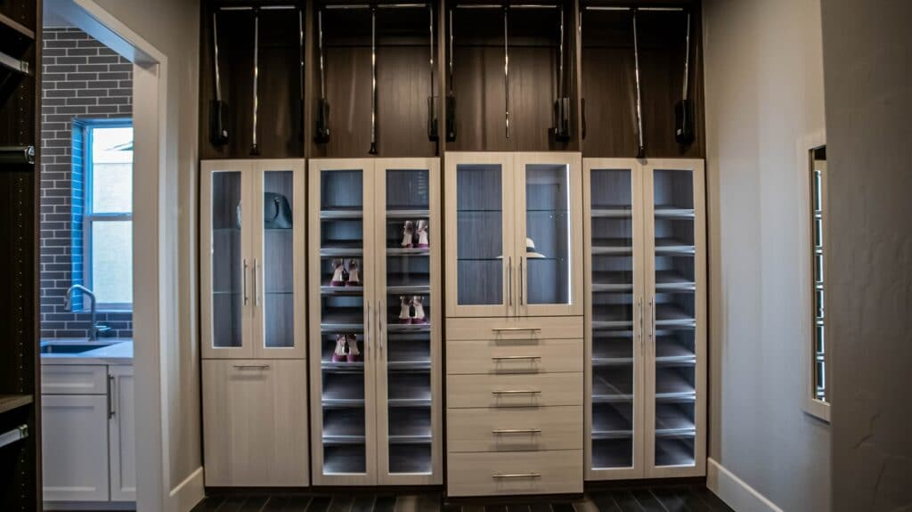 Two luxury shoe racks rest alternately with the clothes shelves in classy glass doors in a master bedroom with his and hers closets in Las Vegas