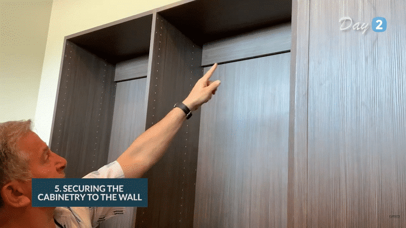 On the 2nd day of closet remodeling, the team secures the cabinet to the wall.