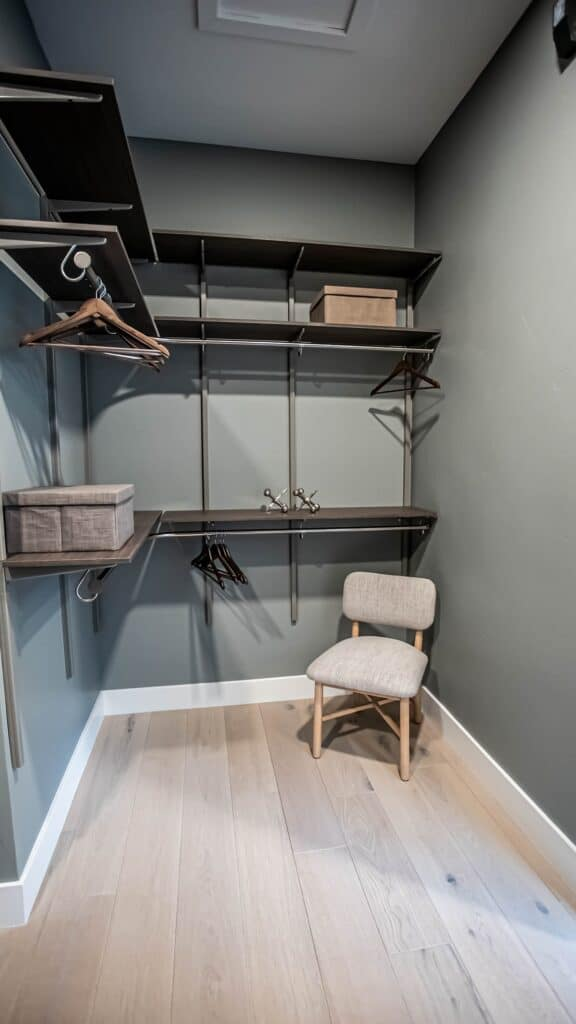 View of his side of the closet with double hang closet rods and shelves.
